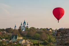 Heißluftballon über dem Feld mit blauem Himmel Lizenzfreies Stockbild