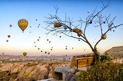 Heißluftballon, der über Felsenlandschaft bei Cappadocia die Türkei fliegt lizenzfreie stockfotos