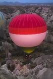 Heißluftballon, der über Felsenlandschaft bei Cappadocia die Türkei fliegt Lizenzfreies Stockbild