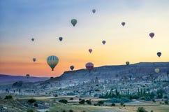 Heißluftballon, der über Felsenlandschaft bei Cappadocia die Türkei fliegt stockbilder