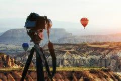 Heißluftballon, der über Felsenlandschaft bei der Türkei fliegt DSLR-Kamera auf einem Stativ im Vordergrund Lizenzfreies Stockfoto