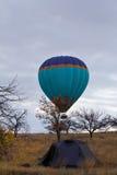 Heißluftballon, der über touristisches Zelt bei Cappadocia die Türkei fliegt Lizenzfreie Stockfotografie