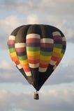 Heißluftballon, der unter Wolken schwimmt Lizenzfreies Stockfoto