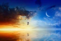 Heißluftballon fliegt in glühenden Sonnenunterganghimmel über ruhigem See Stockbilder