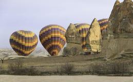 Heißluftballon hinter Felsen in der Wüste Stockfotografie