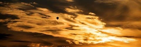 Heißluftballon im Sonnenuntergang mit drastischen Wolken und Farben Stockfotos