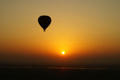 Heißluftballon am Sonnenuntergang lizenzfreie stockfotografie