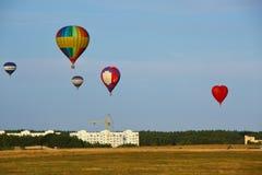 Heißluftballone über dem Feld Lizenzfreie Stockfotos