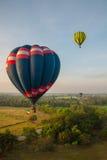 Heißluftballone über grünem Reisfeld Stockbilder