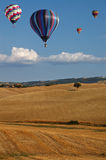 Heißluftballone über toskanischer Landschaft lizenzfreies stockfoto
