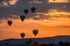 Heißluftballone entfernen sich bei Sonnenaufgang über Cappadocia, Goreme, die Türkei stockfotografie