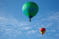 Heißluftballone mit Leuten fliegen Lizenzfreie Stockfotos