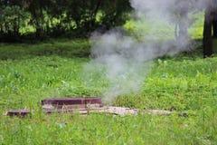 Heißwasser des Abbruchsrohres unter der Luke Dampf und grünes Gras Lizenzfreie Stockbilder