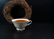 Heißes Teeschale weißes porselain mit runder Weidenkranzdekoration am schwarzen hölzernen Hintergrund/Retro- stockfoto