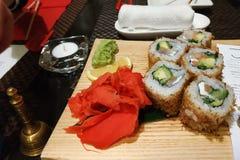Hei?e Sushi werden auf einem h?lzernen Brett mit mariniertem Ingwer und isabi gedient lizenzfreies stockfoto