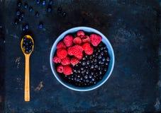 Heidelbeere und Himbeeren in der blauen Schüssel, das Konzept von organischen Beeren rollen auf rostigem Hintergrund der Weinlese lizenzfreies stockbild