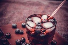 Heidelbeergetränk mit den Beeren und den Eiswürfeln Stockbild