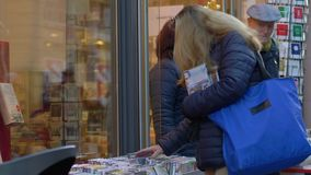 Buyer female film fan chooses new movie disc on street shop window with interesting for home viewing. Heidelberg, Germany - December 12, 2018: buyer female film stock footage