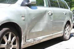 Heavily dent side door on driver`s side of a gray car after crash stock image