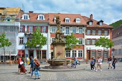 Square called `Kornmarkt` in old city center with fountain with golden Madonna statue and people walking by on sunny day royalty free stock photos