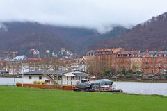 Boat permanently anchored at the Neckar river meadow near city center of Heidelberg, with old buildings and beautiful hill landsca stock images