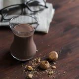 Heiße Schokolade, Mandelgebäck und Zeitungen auf dunkelbrauner Holzoberfläche Lizenzfreie Stockfotografie