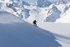 Height. Snowboarder sliding on the slope of the mountain Royalty Free Stock Image