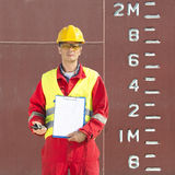 Height of a docker. Docker, standing with a clipboard with a blank page and a cb radio next to the scales and height indication of the hull of a industrial ship royalty free stock photos