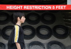 Height Restriction. Image of boy under bright red height restriction bar Royalty Free Stock Images