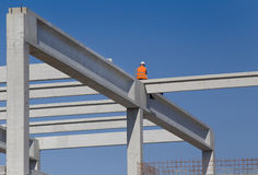 Height worker on building skeleton. Construction worker sitting on concrete beam on height and waiting crane to lift truss for installation Stock Photography