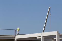 Height worker on building skeleton. Construction worker standing on concrete beam on height and waiting crane to lift truss for installation Royalty Free Stock Image