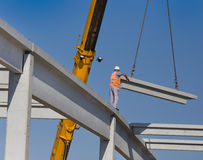 Height worker placing truss on building skeleton. Construction worker standing on concrete beam on height and placing truss lifted by crane Royalty Free Stock Photo