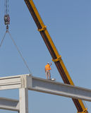 Height worker placing truss on building skeleton Royalty Free Stock Photography