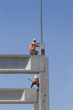 Height worker placing truss on building skeleton Stock Images