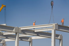 Height worker standing on truss on building skeleton. Construction workers standing on concrete beam on height and placing truss lifted by crane Royalty Free Stock Photo