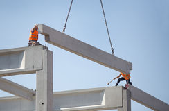 Height workers placing truss on building skeleton Royalty Free Stock Images
