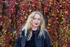 Heikle blonde Frau mit bunten Blättern auf Hintergrund Lizenzfreies Stockfoto