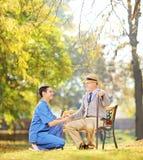 Heilberufler, der dem älteren Mann draußen sitzt hilft Stockfotografie