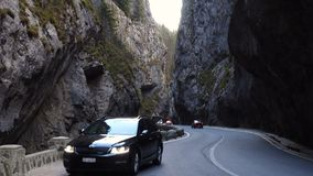 Cars on a road at the famous romanian canyon Cheile Bicazului. СHEILE BICAZULUI, ROMANIA - OCTOBER 31, 2017: cars on a road at the famous romanian canyon Cheile stock video footage