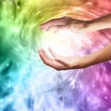 Heilende Hände mit vibrierender Regenbogenturbulenz stockfoto
