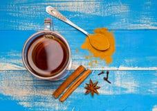 Heilender Tee mit Gewürzen auf einem blauen hölzernen Hintergrund Spitze der Ansicht stockbild