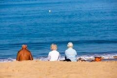 Heilig-Jean de Luze, Frankreich - Sept. 28, 2016: Familie, die auf Badetüchern im Sand sitzt Drei Personen, ein Mann und zwei Fra Lizenzfreies Stockfoto
