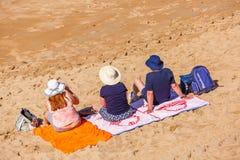 Heilig-Jean de Luze, Frankreich - Sept. 28, 2016: Familie, die auf Badetüchern im Sand sitzt Drei Personen, ein Mann und zwei Fra Lizenzfreie Stockfotos