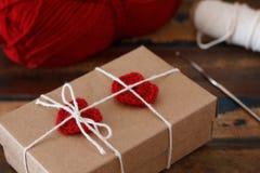 Heilig-Valentinsgrußdekoration: rotes Herz der handgemachten Häkelarbeit auf Geschenk p stockfotos