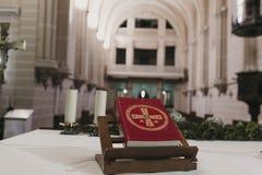 Heilige Bibel auf Tabelle während einer Heiratszeremoniebrautmesse Buch und Kreuz Katholische Verzierungen des heiligen Abendmahl stockbild
