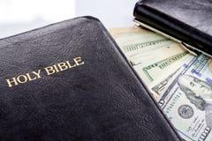 Heilige Bibel und Geld Stockfotos