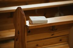Heilige Bijbel in een Witboekdekking op een houten bank in kerk stock afbeeldingen