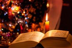 Heilige Bijbel met kaars op bokeh Royalty-vrije Stock Foto