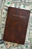 Heilige bijbel op ons dollars Stock Afbeelding
