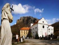 Heilige John die dwarsstandbeeld en kerk houden royalty-vrije stock foto's